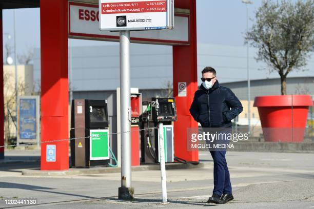 Man wearing a surgical mask walks past a petrol station in Codogno, southeast of Milan, on February 22, 2020. - Streets were deserted and residents...