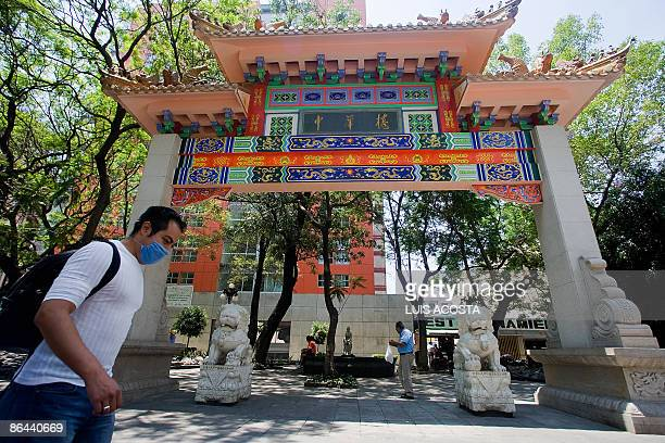 A man wearing a surgical mask walks past the entrance of Mexico City's Chinatown on May 6 2009 Mexico emerged Wednesday from a fiveday lockdown...