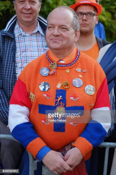 A man wearing a sweater with brooches of the Dutch King WillemAlexander Queen Maxima and other royal families is pictured ahead of the Prinsjesdag in...
