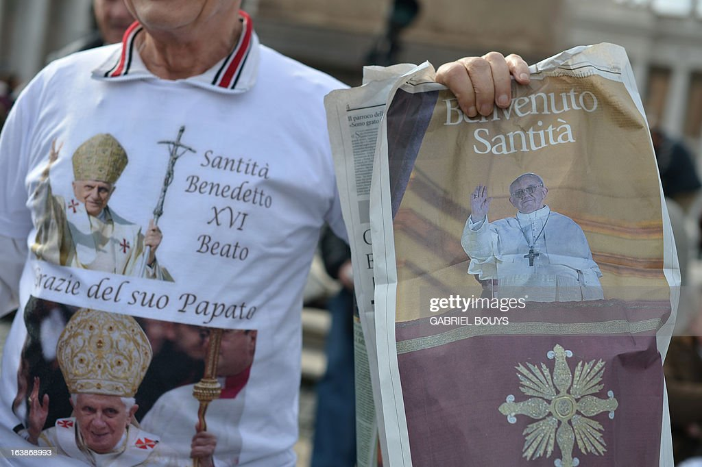 A man wearing a tee-shirt with pictures of Pope Benedict XVI shows a picture of Pope Francis as he waits for pope's first Angelus prayer at St Peter's square on March 17, 2013 at the Vatican. Pope Francis begins his papacy in earnest today ahead of his formal inauguration mass, with a weekly prayer address used by previous pontiffs to comment on international affairs. The pope's first Angelus prayer, delivered from a window high above St Peter's Square, is a chance for the first Latin American pontiff to begin to sketch out a more global vision for the role of the Roman Catholic Church.