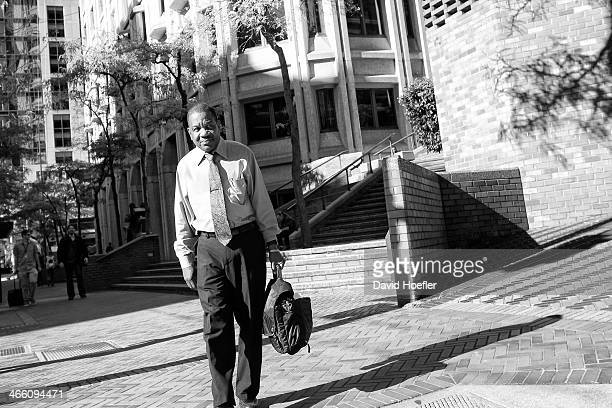 CONTENT] Man wearing a tie walking down the sidewalk with a bag