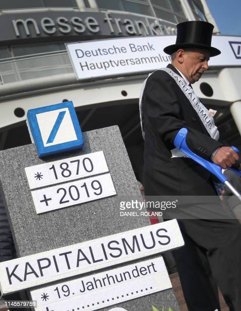 A man wearing a top hat protests near a tomb stone mockup showing the logo of the German company Deutsche Bank in front of the Messehalle prior to...