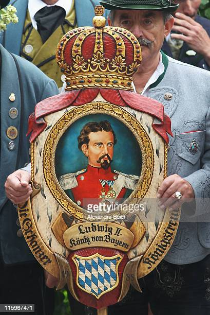 A man wearing a traditional Bavarian costume holds asign showing King Ludwig II during a religious mass to be held in honour of the 125th anniversary...