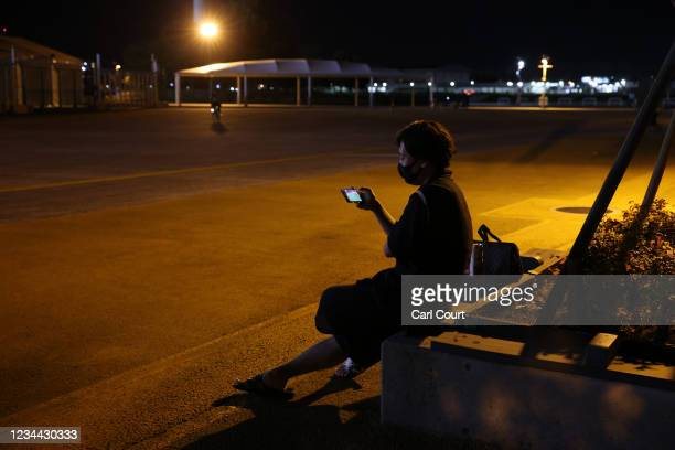 Man wearing a traditional Japanese jinbei watches Japans mens semi-final match against Spain on a smartphone outside Saitama Stadium where the game...