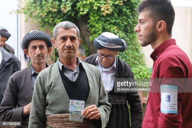 A man wearing a traditional Kurdish outfit shows his identity and voting cards before entering a polling station in the Iraqi Kurdish city of...