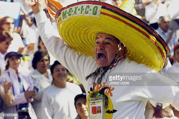 A man wearing a traditional Mexican sombrero cheers as Pope John Paul II enters the Azteca stadium in the popemobile to attend a rally described as...