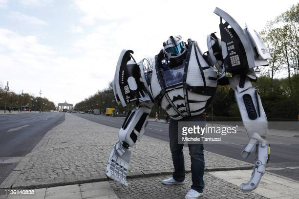 A man wearing a transformers costume with the Gamescom logo walks along the Strasse des 17 Juni street ahead of the Taxi protest on April 10 2019 in...