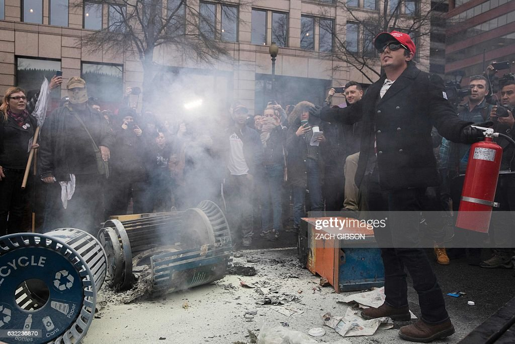 TOPSHOT - A man wearing a Trump hat extinguishes a garbage fire during a protest reacting to the inauguration of US President Donald Trump on January 20, 2017 in Washington, DC. / AFP / ZACH