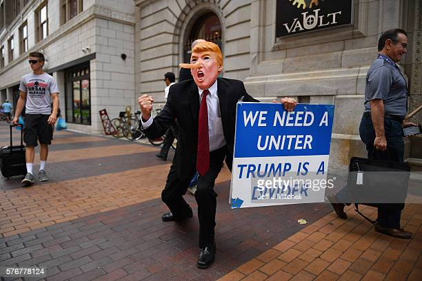 A man wearing a trump mask walks through downtown on July 17 2016 in Cleveland Ohio An estimated 50000 people are expected in Cleveland including...