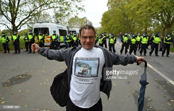 Man wearing a t-shirt stating that the 9/11 September 11 terror attacks on the Twin Towers in New York was a conspiracy, poses for a photograph ahead...