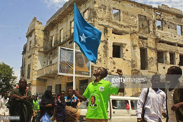 A man wearing a tshirt with a picture of newly elected Somali President Hassan Sheikh Mohamud on it waves a Somali flag as he celebrates in southern...