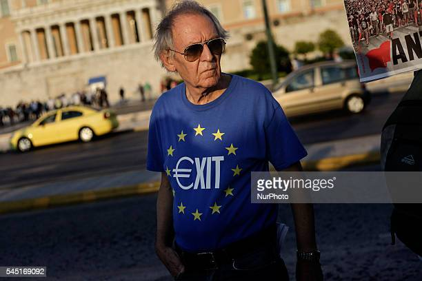 A man wearing a tshirt with the EU flag and the word Exit depicting the Euro sign during a demonstration for one year after the Greek referendum...