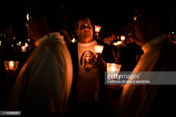 A man wearing a tshirt with the image of Our Lady Fatima holds a candle during the candle procession at the Fatima shrine in Fatima central Portugal...