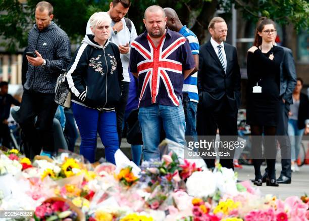 A man wearing a Union Flagthemed shirt looks at flowers placed at the south side of London Bridge close to Borough Market in London on June 5 in...