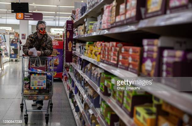 Man wearing a Union Jack flag design face mask shops in a Sainsburys supermarket on January 12, 2021 in Tunbridge Wells, United Kingdom. In response...