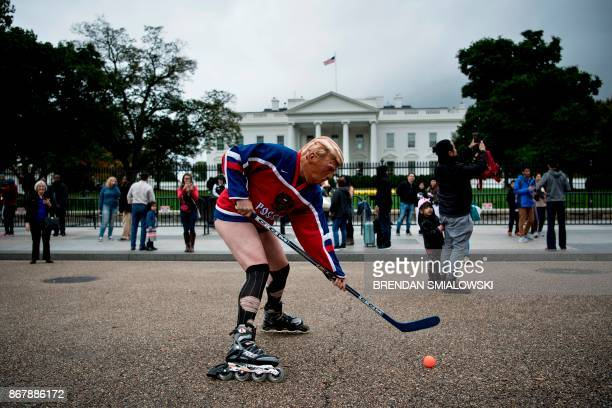 A man wearing a US President Donald Trump mask and a Russian hockey jersey stages a protest outside the White House on Pennsylvania Avenue in...