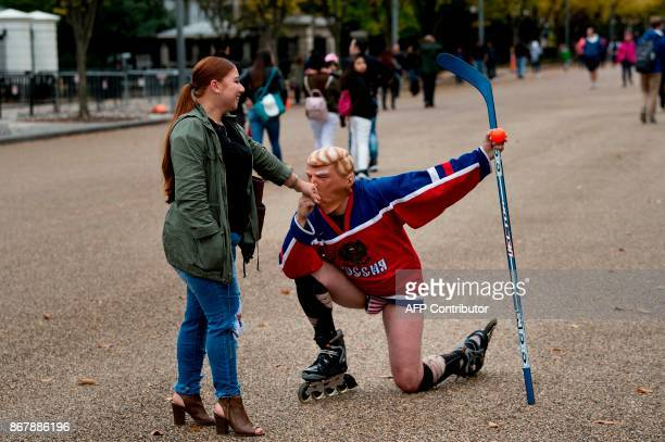 A man wearing a US President Donald Trump mask and a Russian hockey jersey kisses a passerby's hand while staging a protest outside the White House...