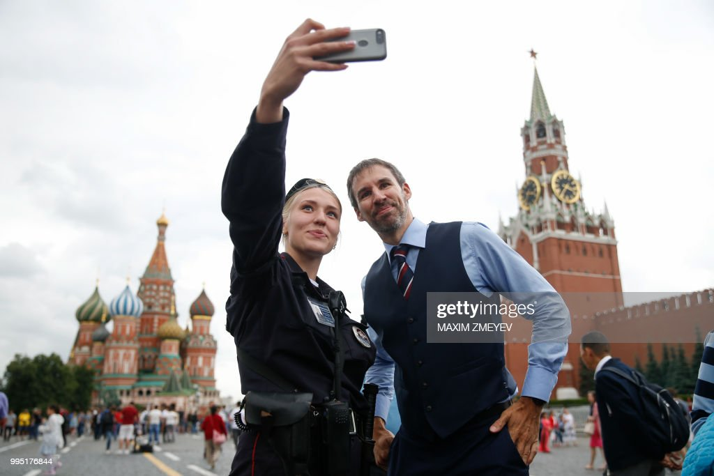 a man wearing a waistcoat poses for a selfie with a police officer