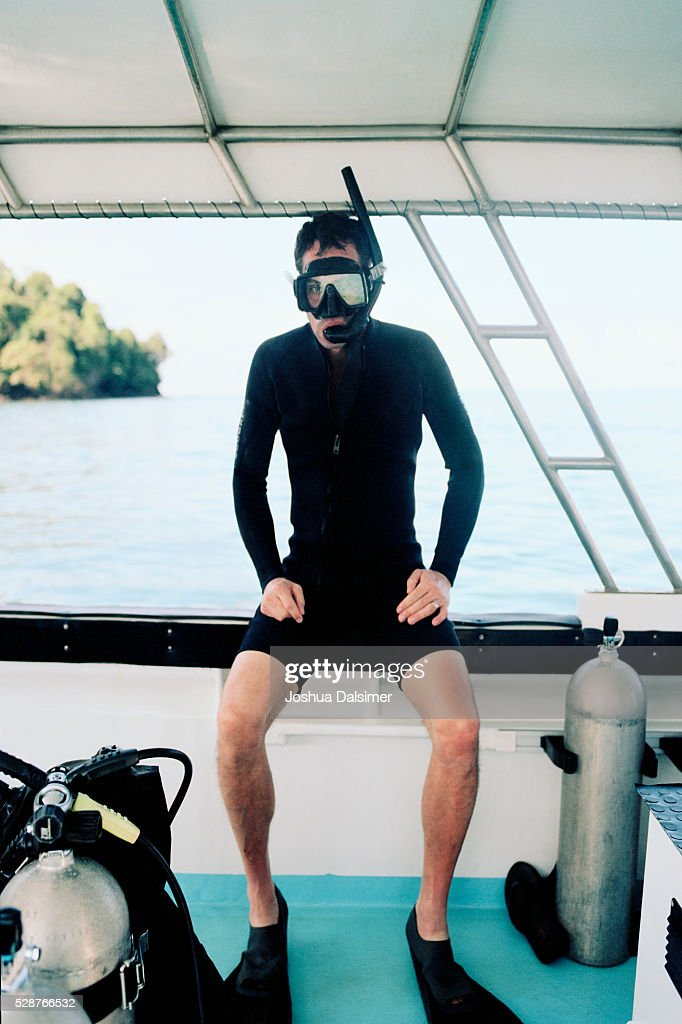 Man wearing a wet suit on a boat : Stock Photo