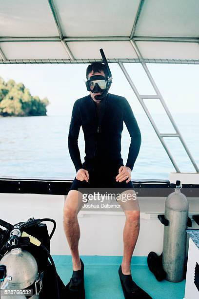 Man wearing a wet suit on a boat