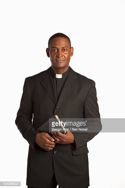 A Man Wearing A White Clerical Collar Holding A Bible