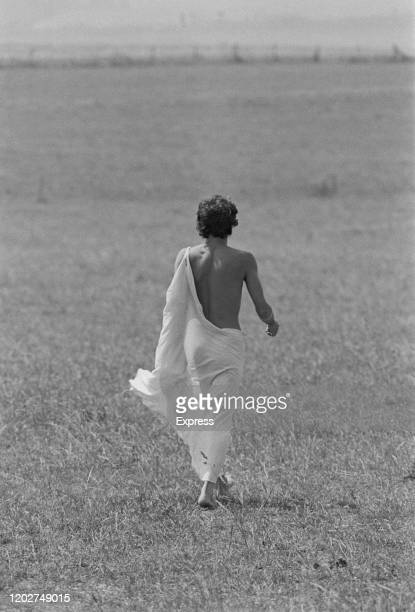 A man wearing a white toga walking with his back to the camera across the site of the Watchfield Free Festival in Watchfield Oxfordshire August 1975