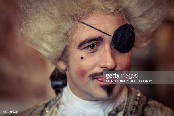 Man wearing a wig and eye patch courtship party with participants wearing clothes from the Louis XIV period Palace of Versailles France Historical...