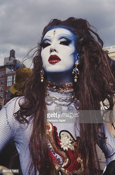 Man wearing a wig and make-up poses for a photograph at the Wigstock festival, New York City, USA, August 1994.