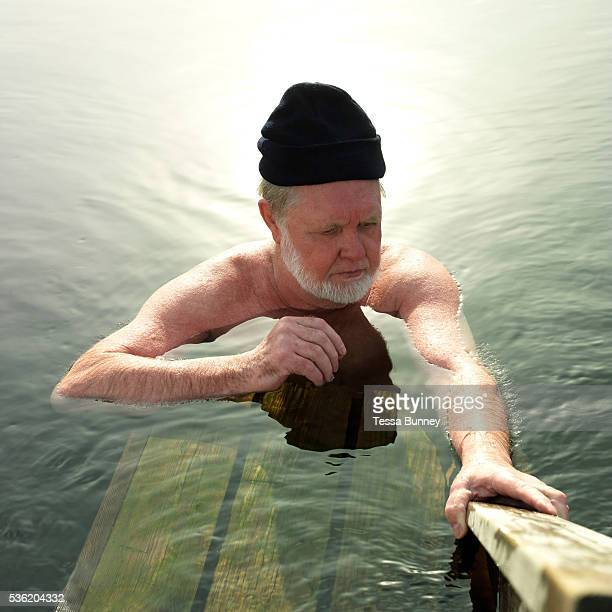 A man wearing a woollen hat relaxes in a hole in the ice after taking a sauna in the small lake Vuorilampi Jyvaskyla Central Finland