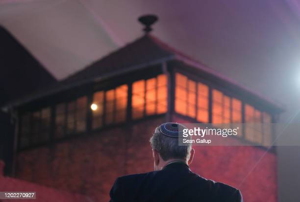 Man wearing a yarmulka stands next to the main tower at the entrance to the former Auschwitz-Birkenau concentration camp, which is covered under a...