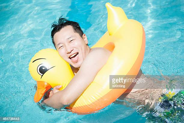 Man wearing a yellow duck inflatable tube and playing in the pool