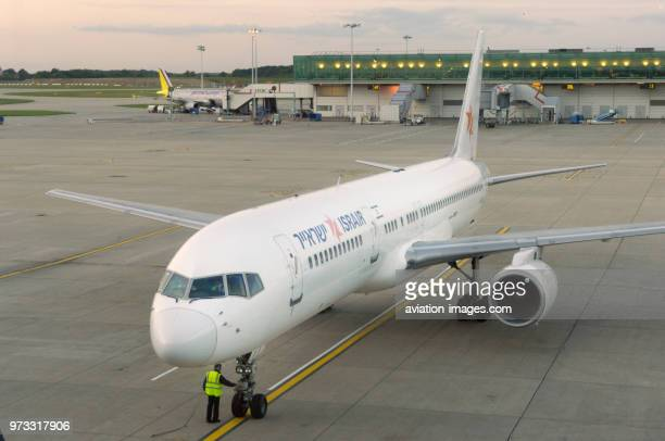 man wearing a yellow highviz tabard by the nosewheel undercarriage of an Israir Boeing 757200 ER parked with a Germanwings Airbus A319 parked at the...