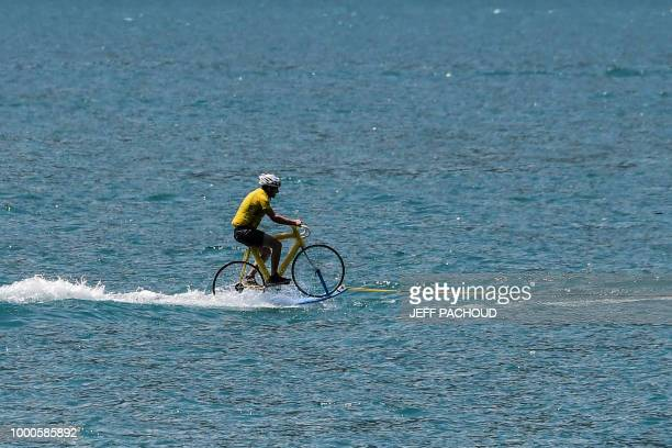 A man wearing a yellow jersey perfoms water skiing on a bicycle on the Lake of Annecy during the tenth stage of the 105th edition of the Tour de...