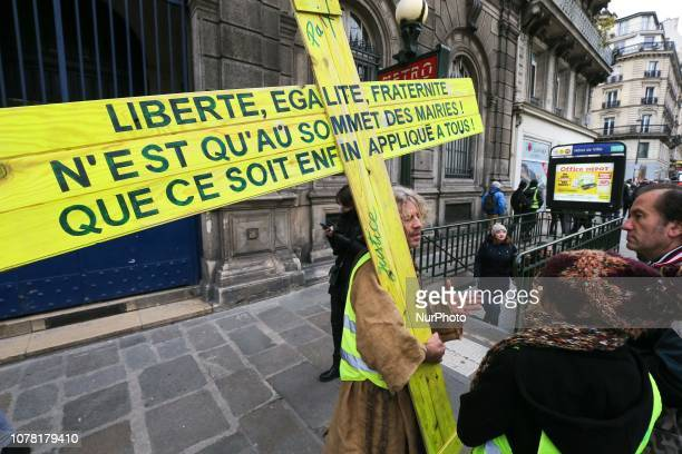 A man wearing a yellow vest carries a yellow cross during a a demonstration called by the yellow vests movement for the eighth week in a row of...