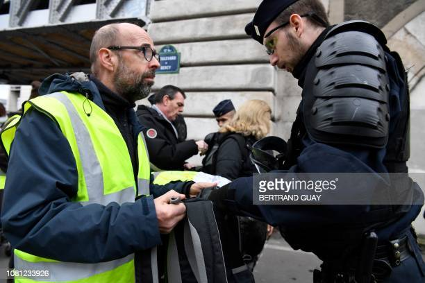 A man wearing a yellow vest holds his bag as a member of security forces conducts searches at the start of a gathering in Bercy in Paris on January...