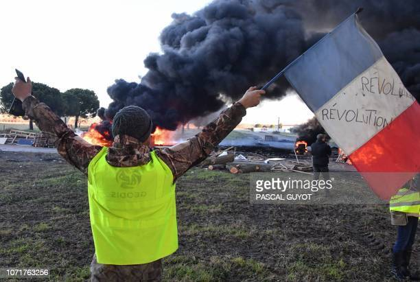 TOPSHOT A man wearing a yellow vest waves a French flag in front of burning tyres at a road blockade during a protest against the rise in the price...