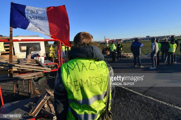 TOPSHOT A man wearing a yellow vest with the inscription Macron resignation stands in front of a road blockade during a demonstration to protest...