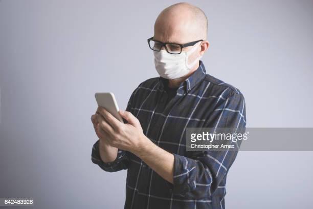 Man met luchtvervuiling gezichtsmasker met behulp van slimme telefoon