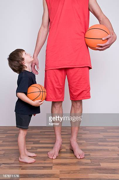 A man wearing all red holding a basketball next to a child