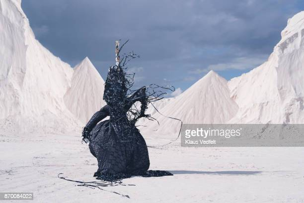 Man wearing amazing costume, made out of old CD's and videotapes - in limestone landscape