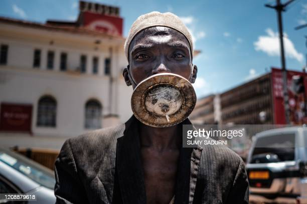 Man wearing an alternative mask poses for a photograph in Kampala, on April 1, 2020. - Ugandan President Yoweri Museveni on March 30 ordered an...