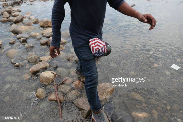 A man wearing an American flag hat on his belt cross through the low waters of the Táchira River near the Simón Bolívar international bridge which...