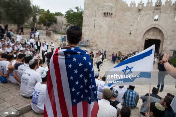 A man wearing an American flag watch the flags march outside Damascus Gate on May 13 2018 in Jerusalem Israel Israel mark Jerusalem Day celebrations...