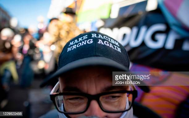 A man wearing an antiracism hat dances in the street along with other demonstrators in celebration for Joe Biden getting elected President of the...