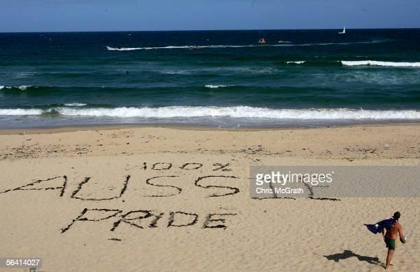 A man wearing an Australian flag walks past a slogan etched into the sand on Cronulla Beach December 11 2005 in Sydney Australia Despite a massive...