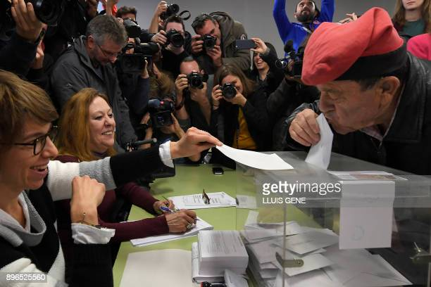 TOPSHOT A man wearing an Catalan barretina hat kisses his ballot before casting his vote for the Catalan regional election at a polling station in...