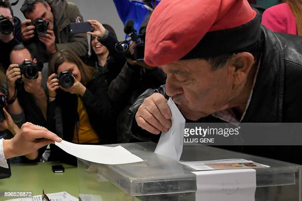 A man wearing an Catalan barretina hat kisses his ballot before casting his vote for the Catalan regional election at a polling station in Barcelona...
