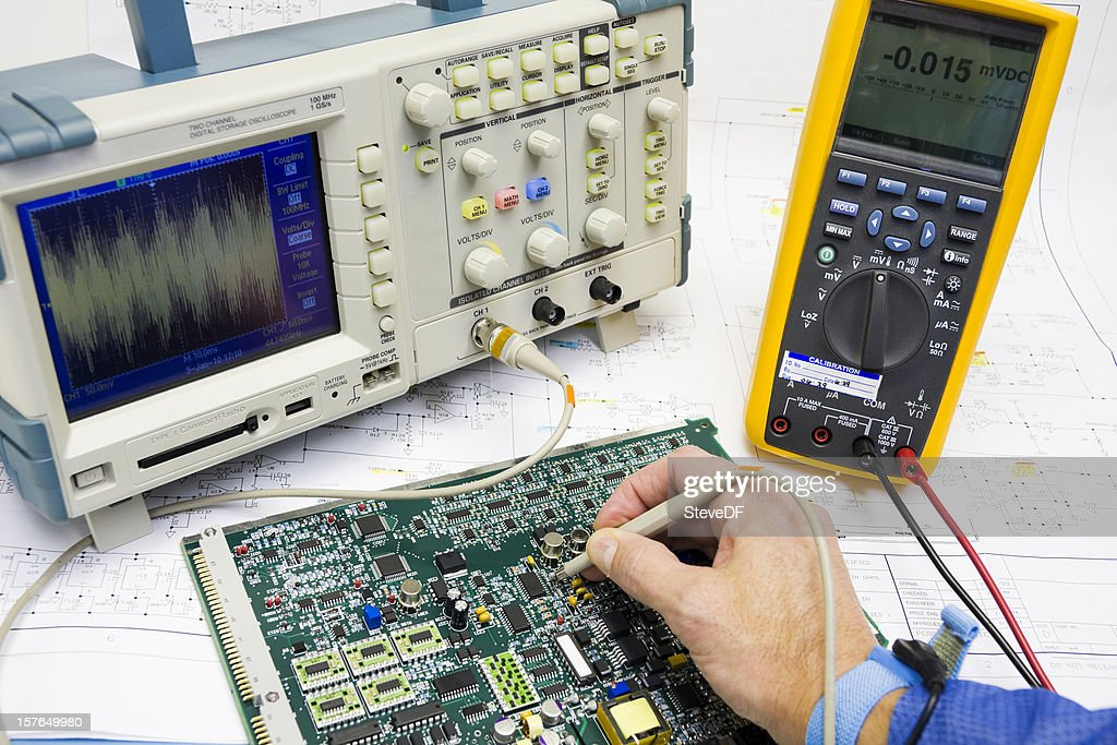 A man wearing an ESD band troubleshoots electronic circuits : Stock Photo
