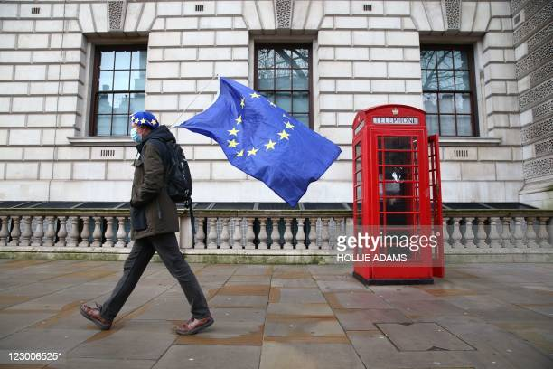 Man wearing an EU flag-themed beret and carrying an EU flag is seen on Whitehall in central London on December 11, 2020. - Prime Minister Boris...