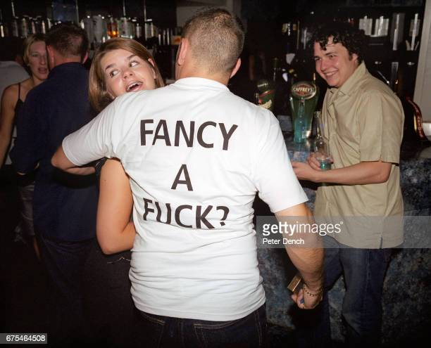 Man wearing an explicit T-shirt attempts to chat to a young woman in a Newquay nightclub. July 2001.